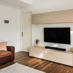 Ispirazione per un piccolo home theatre minimal chiuso con pareti bianche, pavimento in legno massello medio e TV a parete