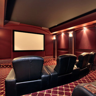 This is an example of a medium sized rustic open plan home cinema in New York with red walls, carpet, a projector screen and red floors.