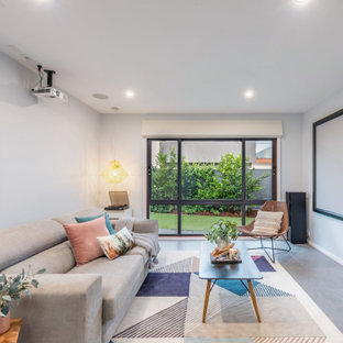 This is an example of a mid-sized contemporary open concept home theatre in Canberra - Queanbeyan with a projector screen.