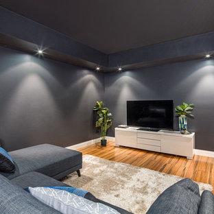 Aménagement d'une salle de cinéma victorienne de taille moyenne et fermée avec un mur noir, un sol en bois clair et un téléviseur fixé au mur.