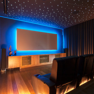 Contemporary enclosed home theatre in Sydney with grey walls, medium hardwood floors, a wall-mounted tv and white floor.