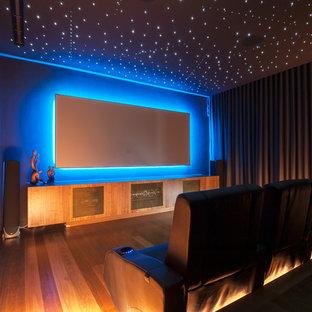 Abgetrenntes Modernes Heimkino mit grauer Wandfarbe, braunem Holzboden, Wand-TV und weißem Boden in Sydney
