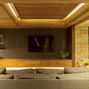 Large contemporary enclosed home theatre in Sydney with grey walls, slate floors and a wall-mounted tv.