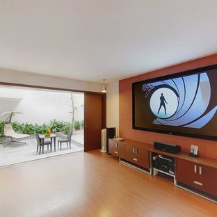 Mid-sized contemporary enclosed home theatre in Bengaluru with orange walls, laminate floors and a wall-mounted tv.