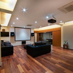 Immagine di un grande home theatre minimal aperto con pareti gialle, pavimento in laminato e schermo di proiezione