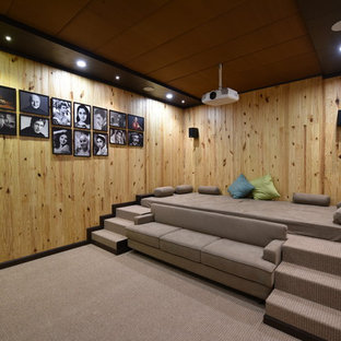 Photo of a contemporary enclosed home theatre in Other with brown walls, carpet, a projector screen and grey floor.