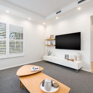 Großes, Offenes Skandinavisches Heimkino mit weißer Wandfarbe, Teppichboden, Wand-TV und grauem Boden in Sonstige