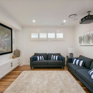 Contemporary enclosed home theatre in Sydney with white walls, medium hardwood floors, a projector screen and brown floor.