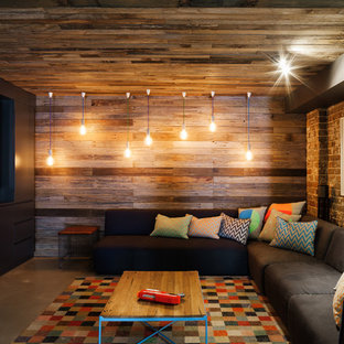 Industrial open concept home theatre in Sydney with multi-coloured walls, concrete floors, a projector screen and grey floor.