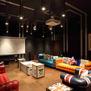 This is an example of a large eclectic enclosed home theatre in Pune with medium hardwood floors, brown floor, black walls and a projector screen.