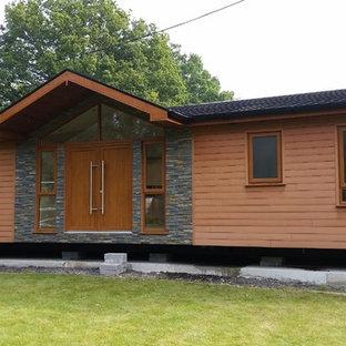 Imagen de fachada marrón, minimalista, grande, de una planta, con revestimientos combinados y tejado a dos aguas