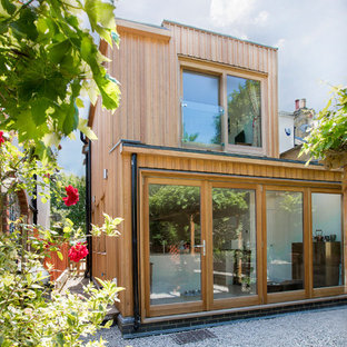 Medium sized and beige contemporary two floor exterior in London with wood cladding and a flat roof.