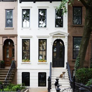 На фото: трехэтажный, белый таунхаус в стиле современная классика