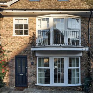 Ejemplo de fachada de casa pareada moderna, pequeña, de tres plantas, con revestimiento de ladrillo, tejado a dos aguas y tejado de teja de barro