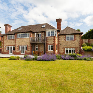 Large and beige classic detached house in Surrey with three floors and stone cladding.