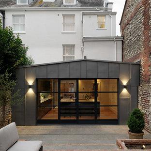 Immagine della facciata di una casa bifamiliare piccola grigia contemporanea a tre o più piani con rivestimento in metallo, tetto a capanna e copertura in metallo o lamiera