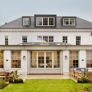 Photo of a large and white traditional render detached house in London with a shingle roof.