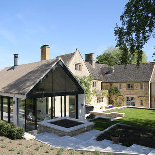 Design ideas for a medium sized and beige country two floor detached house in Gloucestershire with stone cladding, a pitched roof and a shingle roof.