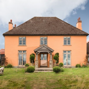 Example of a large country orange three-story stucco house exterior design in Other with a hip roof and a shingle roof