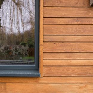 Foto de fachada blanca, contemporánea, de tamaño medio, de dos plantas, con revestimiento de madera y tejado a dos aguas