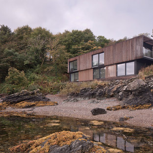 Photo of a brown beach style two floor detached house in Other with wood cladding and a flat roof.