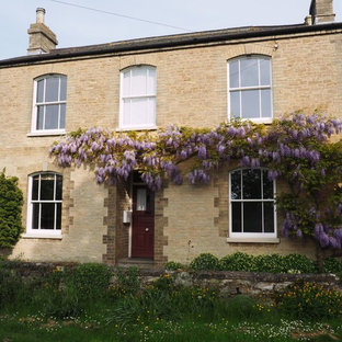 Medium sized and beige traditional two floor house exterior in Buckinghamshire with stone cladding.