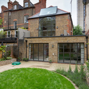 This is an example of a medium sized and beige contemporary two floor brick terraced house in London with a hip roof.
