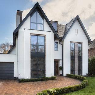 Modelo de fachada blanca, actual, grande, de tres plantas, con revestimientos combinados y tejado a dos aguas