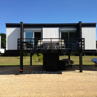 This is an example of a small and white coastal one floor exterior in Sussex with mixed cladding and a flat roof.