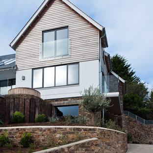 Diseño de fachada de casa marinera, de tres plantas, con revestimiento de madera, tejado a dos aguas y tejado de teja de barro
