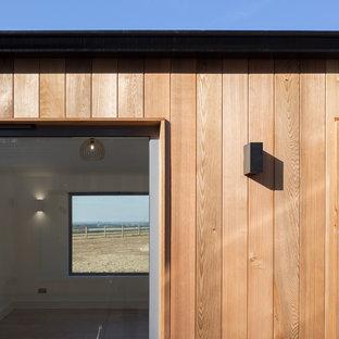 Diseño de fachada naranja, industrial, con revestimiento de madera y tejado de teja de barro