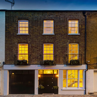Large trendy gray three-story brick exterior home photo in London with a metal roof