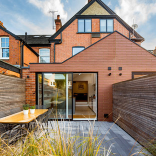 This is an example of a medium sized and red classic brick terraced house in London with three floors and a pitched roof.