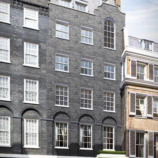 Modelo de fachada de casa pareada negra, clásica, extra grande, de tres plantas, con revestimiento de ladrillo, tejado a doble faldón y tejado de teja de barro