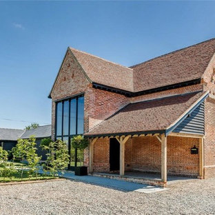 This is an example of a large and red contemporary brick detached house in Hertfordshire with three floors.