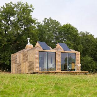 Ispirazione per la micro casa piccola rustica a un piano con rivestimento in legno