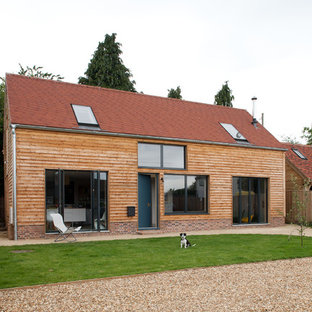 This is an example of a medium sized and beige scandi detached house in Buckinghamshire with three or more floors, wood cladding and a pitched roof.