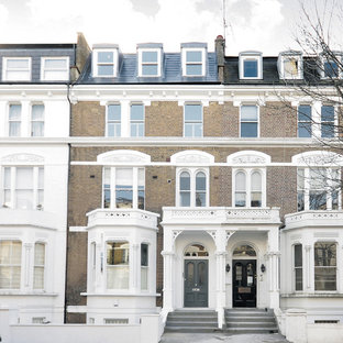 Photo of a brown traditional brick terraced house in London with three floors and a pitched roof.