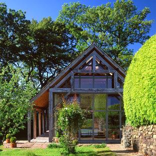Foto de fachada de estilo de casa de campo, de una planta, con revestimiento de vidrio y tejado a dos aguas