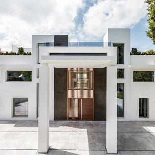 Ejemplo de fachada de casa blanca, actual, grande, de tres plantas, con revestimientos combinados y tejado plano