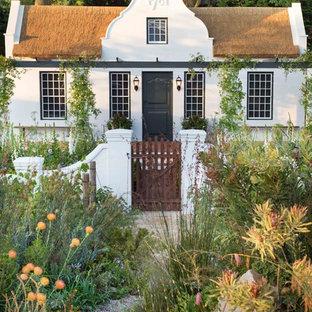 На фото: белый, маленький, двухэтажный частный загородный дом в стиле кантри с двускатной крышей