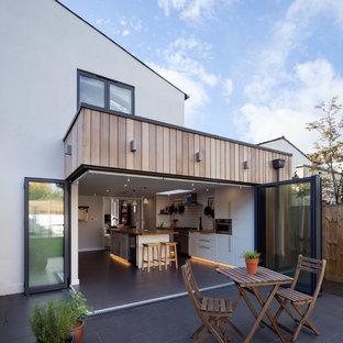 Aménagement d'une façade de maison blanche classique de taille moyenne et à un étage avec un revêtement mixte.