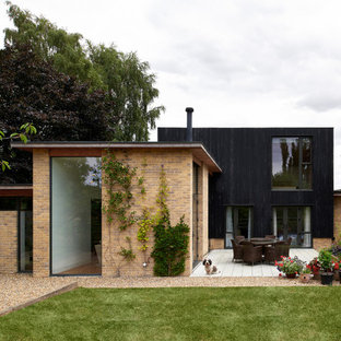 Inspiration for a medium sized and multi-coloured contemporary two floor detached house in Cambridgeshire with a flat roof, a green roof and mixed cladding.