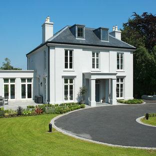 На фото: трехэтажный, серый частный загородный дом в стиле современная классика с облицовкой из цементной штукатурки, вальмовой крышей и металлической крышей с