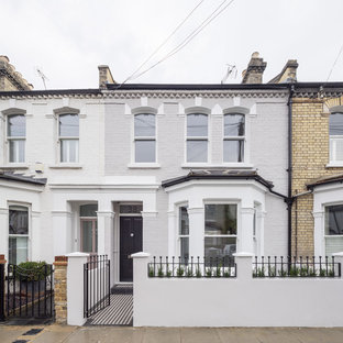 Photo of a gey classic two floor brick terraced house in London.