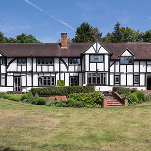 Photo of a large and white traditional two floor detached house in Surrey with mixed cladding, a half-hip roof and a shingle roof.