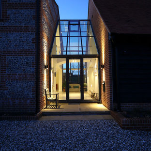 Photo of a red contemporary two floor brick exterior in Other with a pitched roof.