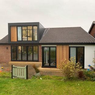 Bild på ett litet funkis svart hus, med två våningar, stuckatur och platt tak