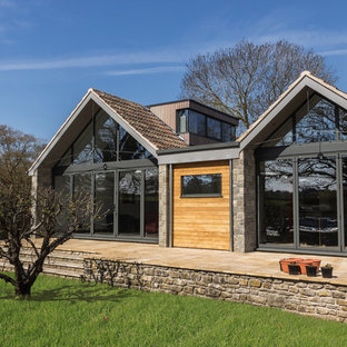 Contemporary exterior in Other with stone cladding and a pitched roof.