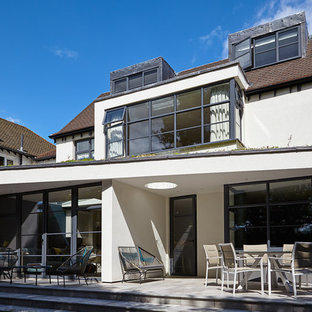 This is an example of a medium sized and white contemporary two floor render detached house in London with a tiled roof.